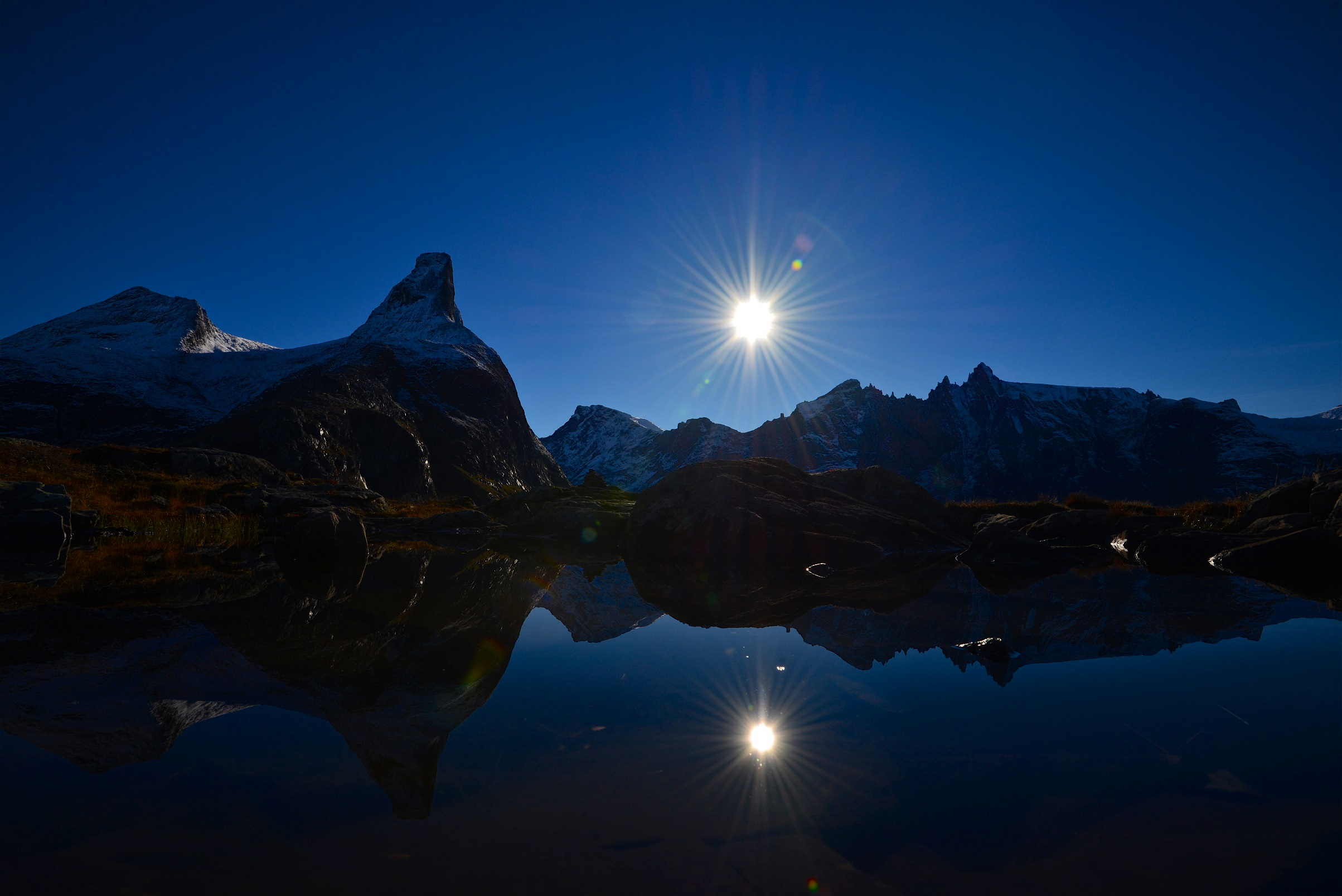 Motsol fjell vann blå himmel