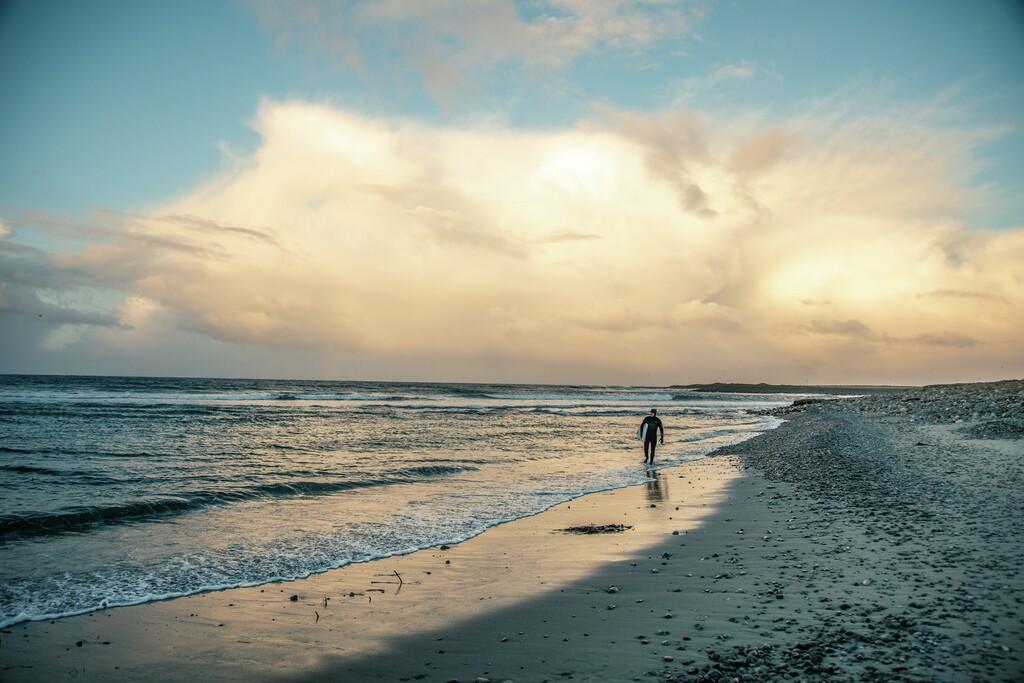 Mann på strand med surfebrett Jæren