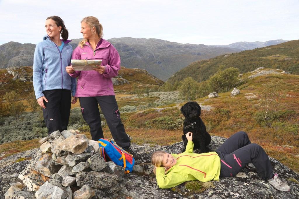 Damer med kart barn som ligger og hviler på fjell med hund
