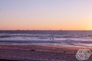The sun setting over the ships off the coast from Cottesloe Beach