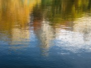 ...and reflections of buildings along Central Park East in the same water, now still.