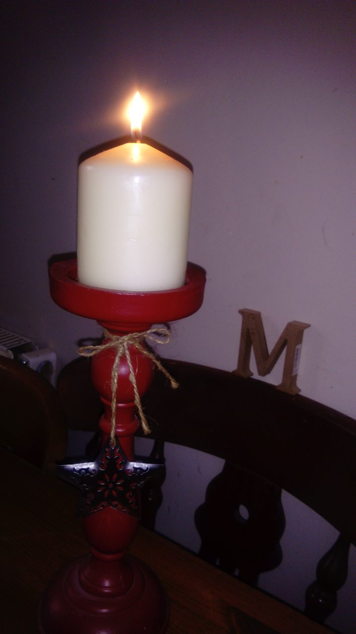 lit candle with an M in the background.