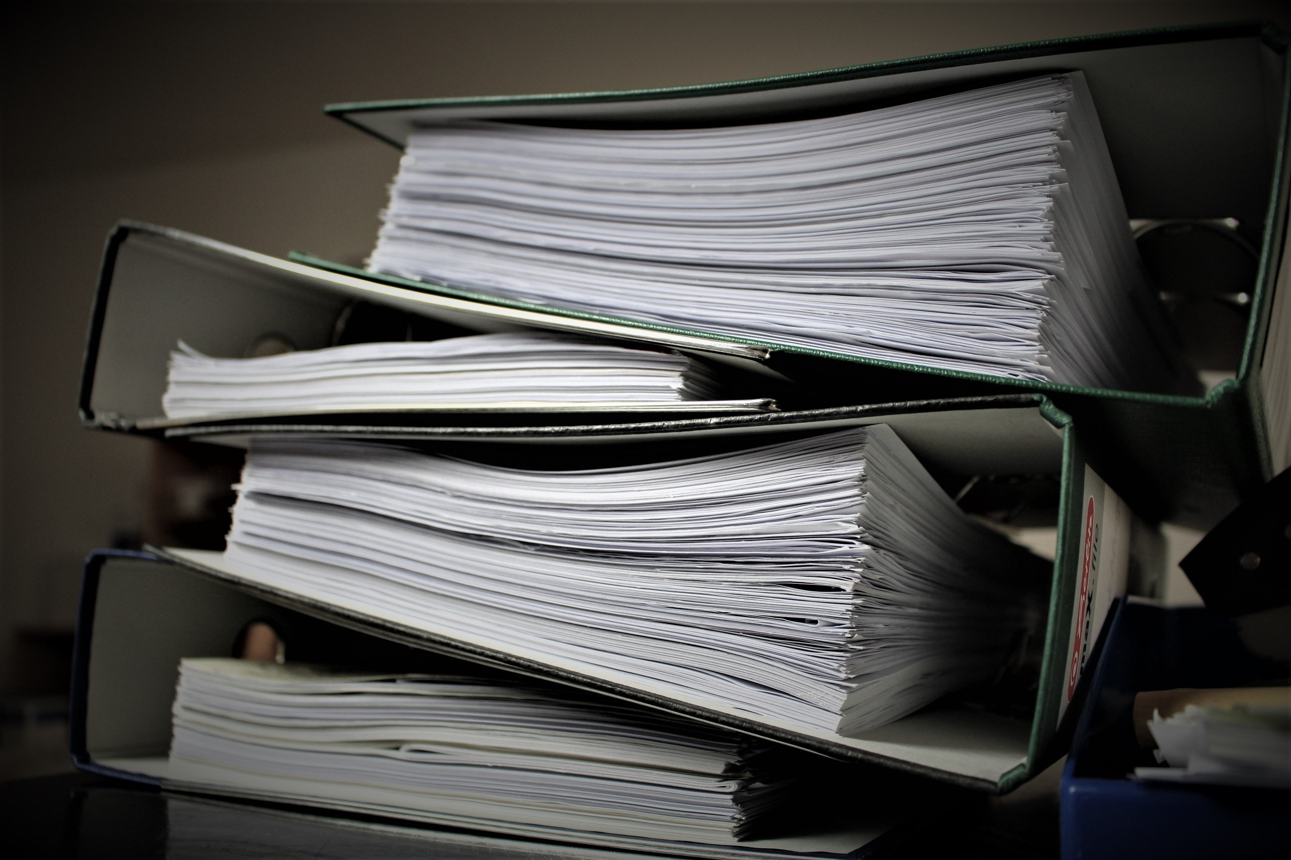 binders full of paperwork stacked in a pile