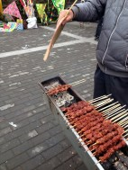 Chuan'r - s street food of ultimate deliciousness! These pork kabobs are cooked over a makeshift grill and seasoned to perfection.