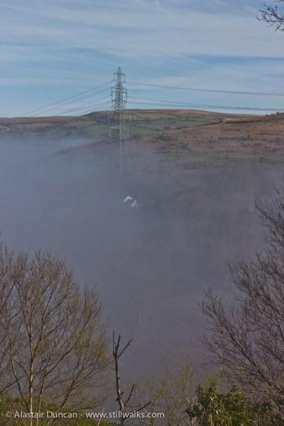 hillside and pylons through mist