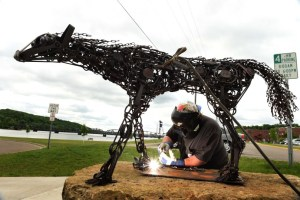 """Welder and artist John Hughes installs """"Trap"""", an original outdoor sculpture of a life-sized female wolf made out of animal traps by Dale Lewis, in downtown Stillwater, Wednesday, June 1, 2016. (Pioneer Press: Scott Takushi)"""