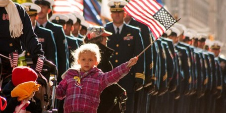 Young child waving a flag at Veterans celebration