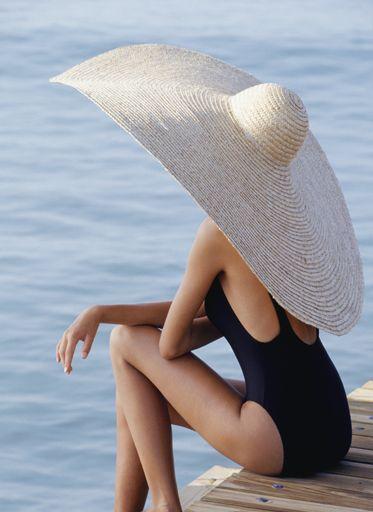 Жінка в солом'яному капелюсі сидить на пірсі