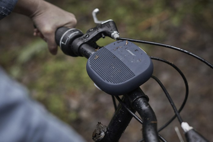 The Bose Soundlink Micro Speaker in Midnight Blue, strapped to the handle of a bike.