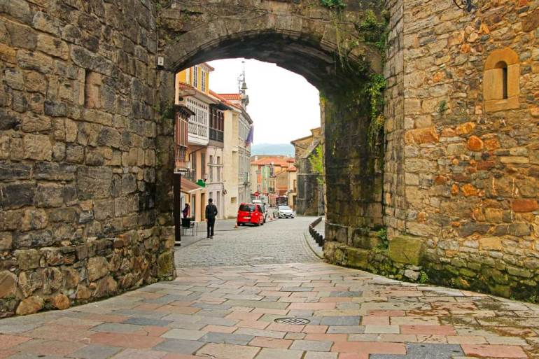 A narrow cobbled street and an old stone wall of Salas, Camino Primitivo, Spain