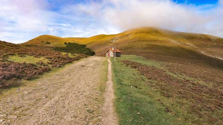 Green mountains, gravel path and clouds - walking over the pass on the Camino Frances
