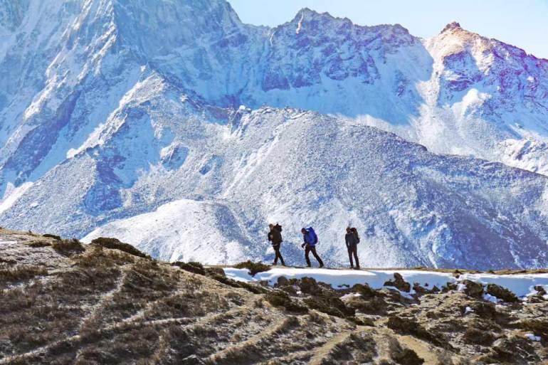 Three trekkers on the Everest Base Camp trek between Dingboche and Lobuche