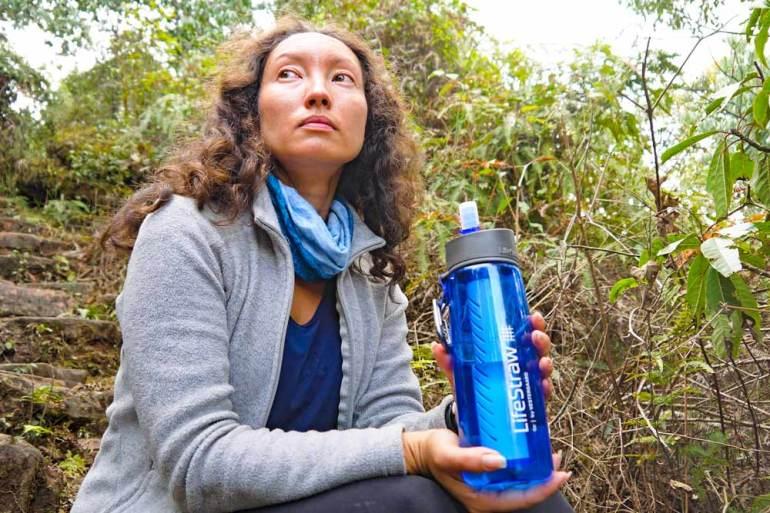 Alya using a LifeStraw bottle on a trek in Nepal