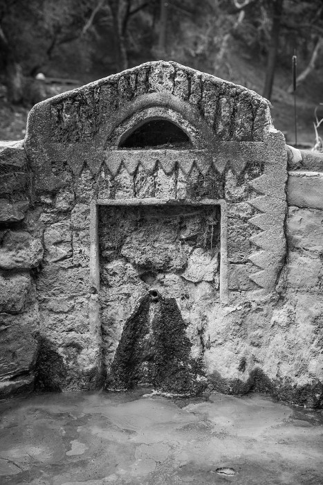 Elaborate carvings surround the outlet on a mineral spring