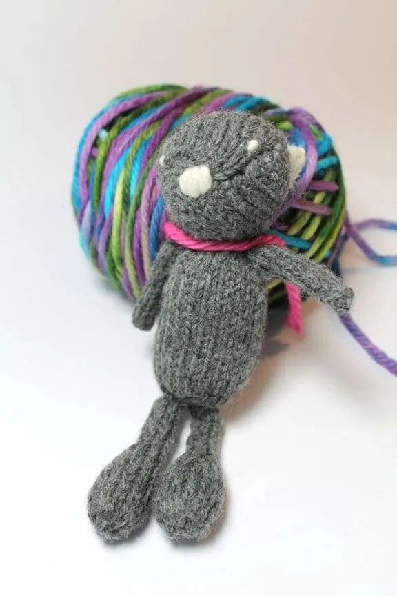 Little bear sitting next to some yarn