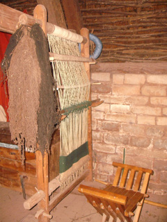 A weaving loom inside one of the cottages