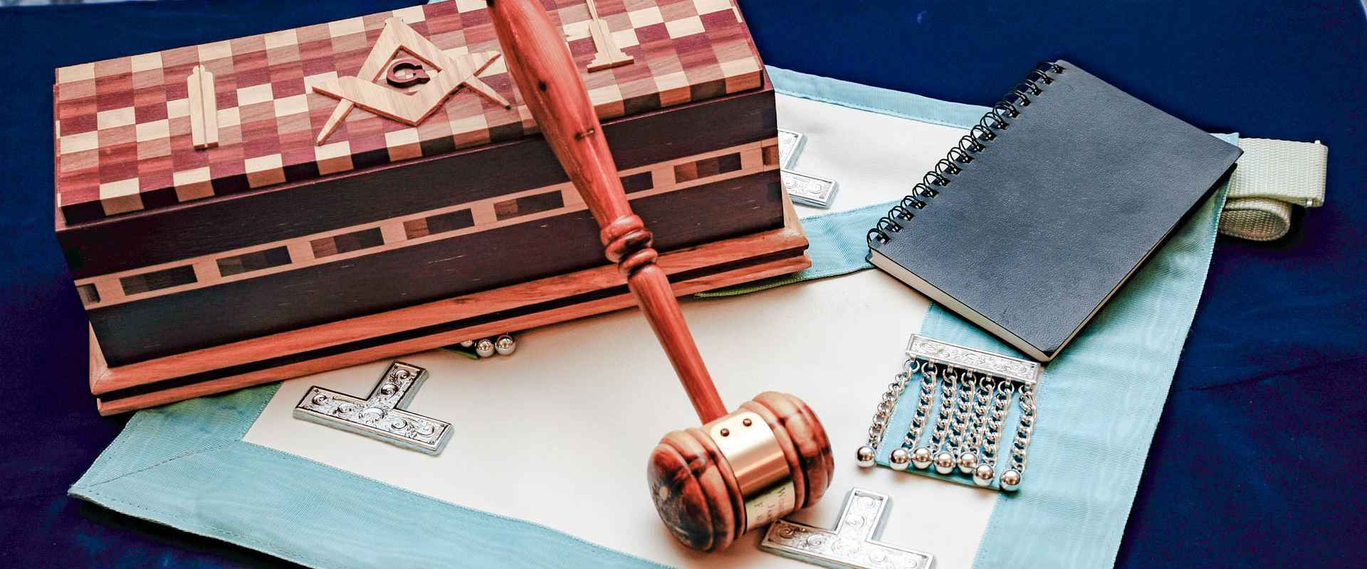 a photograph of the masters gavel, apron and ritual book.