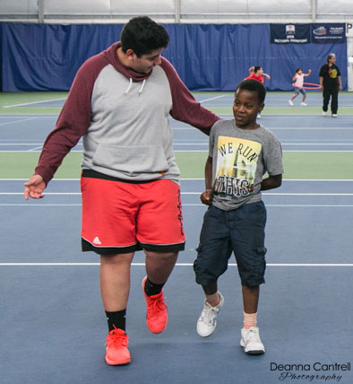A coach and a student on a tennis court.