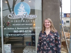 Dr. Melissa Bartoszewski in front of her Stumptown chiropractic office.
