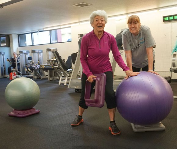 healthy senior citizen working out with trainer at West Coast Fitness