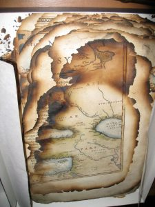 Burnt fragments of the first edition of Ortelius's atlas (1570) – the foremost page shows an area of the Middle East.