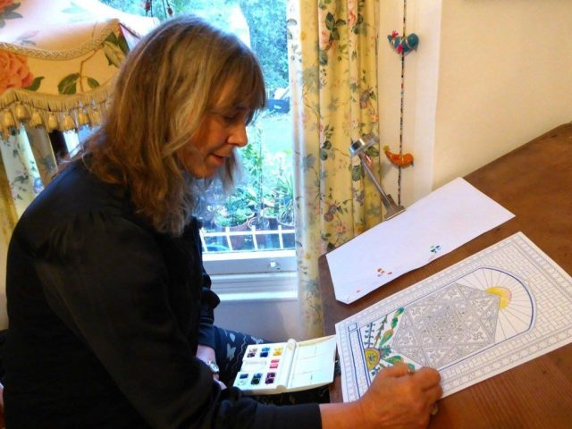Christine painting one of her designs