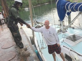 Officer Omari Lewis of the USVI Department of Planning and Environmental Resources shakes hands with Marc Weiser, after Weiser's vessel was salvaged and returned Saturday. (U.S. Coast Guard photo)