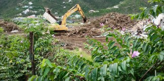 An earth mover sorts debris left by Hurricanes Irma and Maria on St. John.