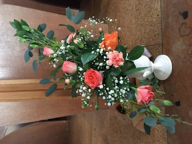 flower arrangement near the pulpit. Pinks, oranges, whites.