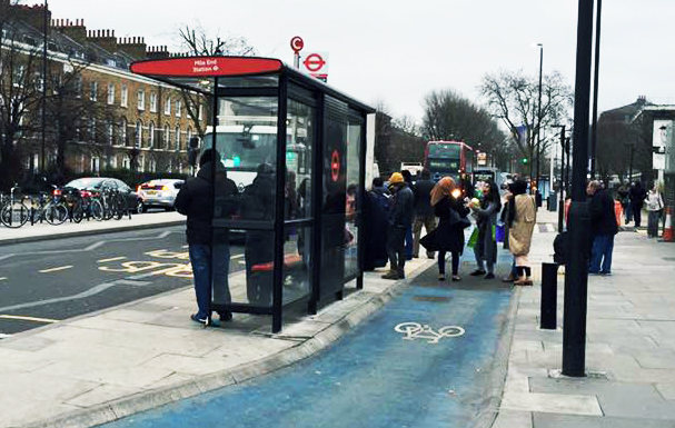 People waiting for a bus at rush hour, texting and chatting, obstructing the new Cycle Superhighway. Photo credit: Valerie Browne