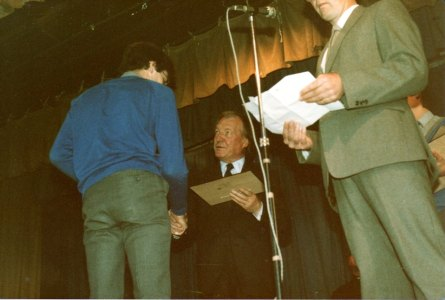 Simon Kidd (Class of 1985) receiving an award (a wooden plaque of school) from Charles Haughey, Leader of the Opposition, 1984. Teacher Brendan Leahy on right.