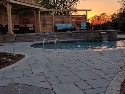 inground pool with the sunset coming down
