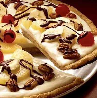 This Banana Split Dessert Pizzais the perfect dessert for any celebration. A sugar cookie crust topped with cream cheese frosting, fruit, nuts, and chocolate sauce!