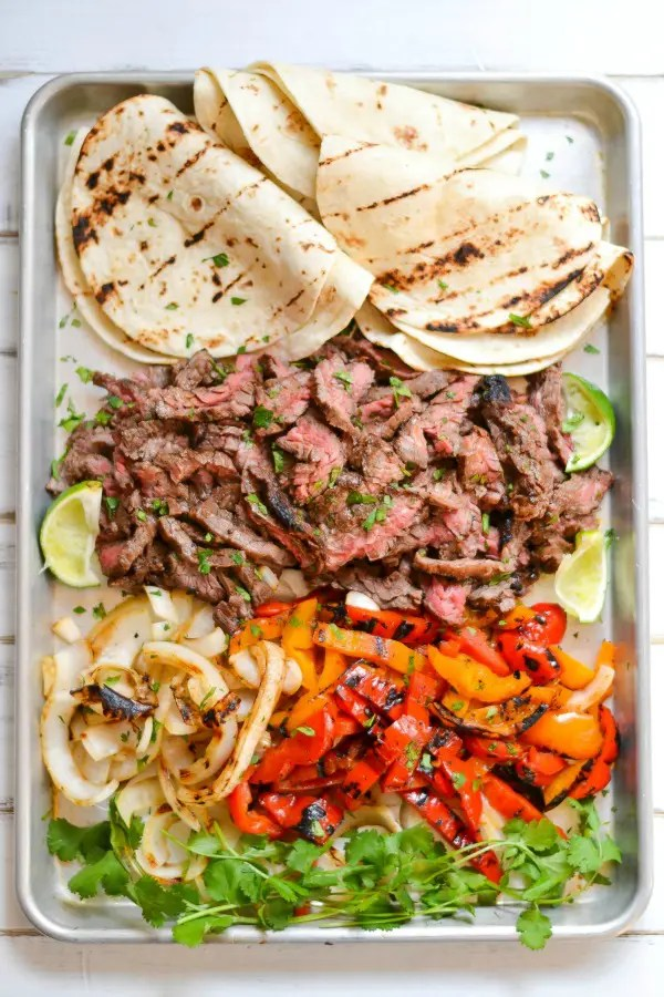 All it takes is a simple marinade and a screaming hot grill to put together this amazing platter of skirt steak fajitas.