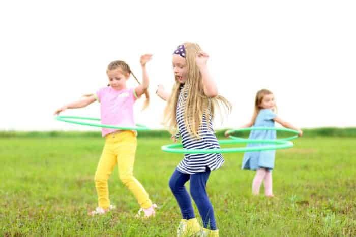 Children having fun with hula hoops outdoor