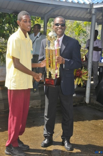 Secondary School Sports is hardly ever mentioned in year end reviews, but 2012 was exceptional for Soufriere Comprehensive Secondary School. So far this term the school won three School Sports titles. Pictured here is Minister Phillip J Pierre presenting the Consolidated Foods Ltd Under-16 Basketball trophy to a team member.