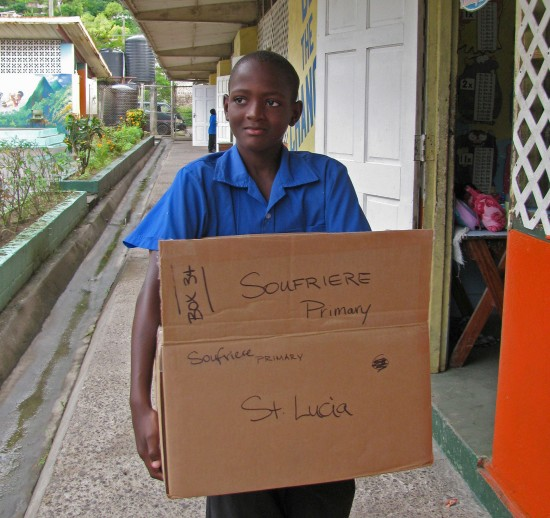 A student carries some of the books that have arrived at the Soufriere Primary School.