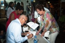 Michael Chastanet signs copies of his books for those who purchased on Saturday.