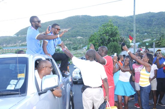 Darren Sammy and Johnson Charles greet fans on Tuesday during motorcade.