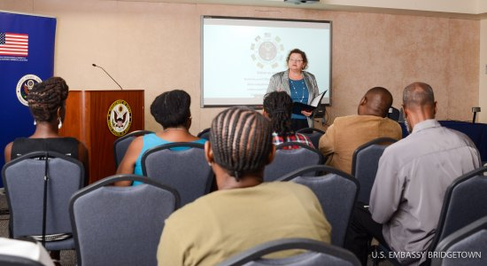 Deputy Chief of the U.S. Mission to Barbados, the Eastern Caribbean, and the OECS Laura Griesmer (standing) delivers remarks to participants at the U.S. Embassy's interactive programme to prevent LGBTI hate crimes.