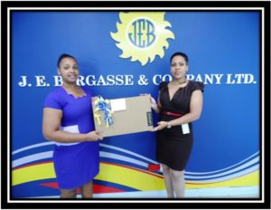Keryahanna Flavion(left) receiving her laptop prize from JE Bergasse