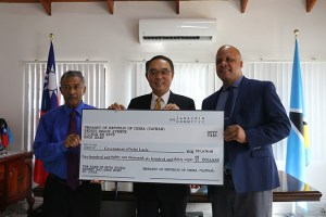 Ambassador Douglas Shen presented check to Hon. Herod Stanislaus, Minister in the Ministry of Agriculture, Fisheries, Physical Planning, Natural Resources and Co-operatives