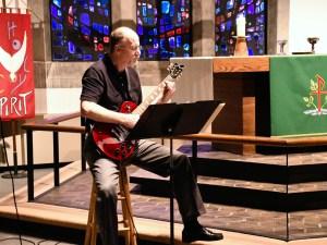 A worship leader playing guitar
