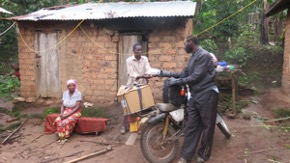 Motorcycle delivery man giving package to another man