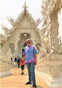 Man standing in front of an ornate Thai temple