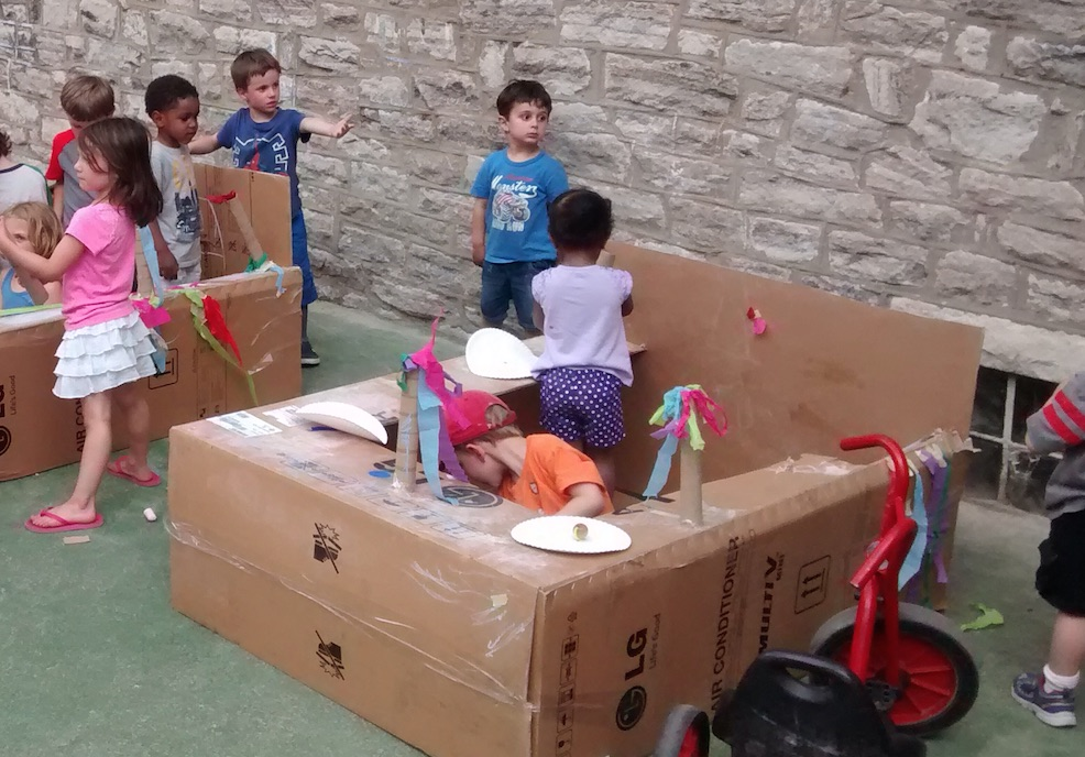 children decorate and build with cardboard boxes