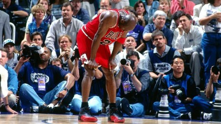 A fatigue Michael Jordan on his knees during game 5 of the 1997 NBA Finals.   Courtesy of Wordpress