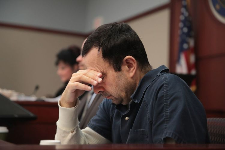 Larry Nassar struggling to face his victims during his trial. | Courtesy of Scott Olson/ Getty