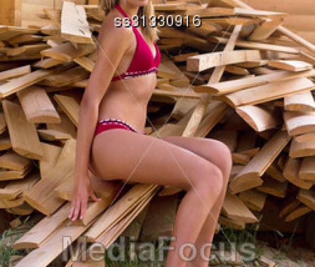Cute Teen Girl Sitting On A Pile Of Planks Stock Photo