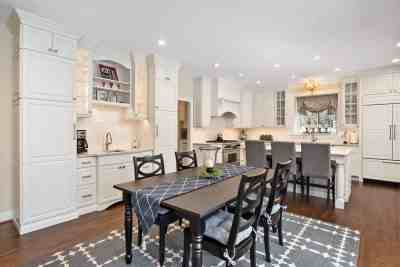 A large kitchen remodel with a new dining table and chairs and kitchen cabinets all around.